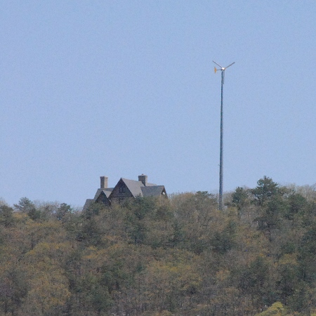 Nice house with windmill on top of the hill next to the fields.